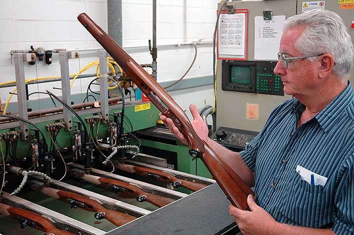At Ruger, an inspector eyes a machine-checkered stock for a Hawkeye rifle. Plain American walnut.